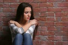 Deprimierte junge Frau auf Ziegelsteinhintergrund Lizenzfreie Stockbilder