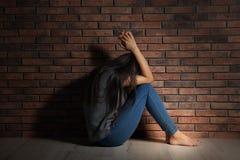 Deprimierte junge Frau, die auf Boden sitzt Stockfotografie