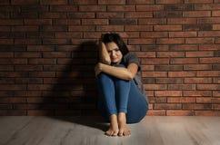 Deprimierte junge Frau, die auf Boden sitzt Stockbilder