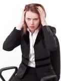 Deprimierte junge Frau, die auf einem Stuhl sitzt. Lizenzfreies Stockfoto
