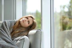 Deprimierte junge Frau, die auf Sofa sitzt Stockfotografie