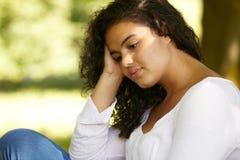 Deprimierte junge Frau, die draußen sitzt Lizenzfreie Stockfotografie