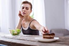 Deprimierte junge Frau, die einen Kuchen wünscht Stockbild