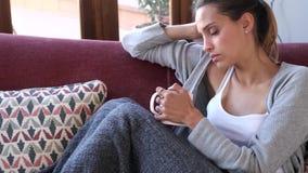 Deprimierte junge Frau, die an ihre Probleme beim Kaffee auf Sofa zu Hause trinken denkt stock video