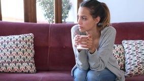 Deprimierte junge Frau, die an ihre Probleme beim Kaffee auf Sofa zu Hause trinken denkt stock video footage