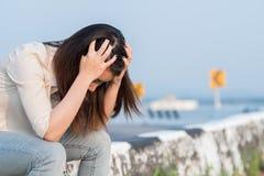 Deprimierte junge Frau, die nahe einer Straße sitzt Lizenzfreies Stockfoto