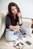 Deprimierte junge Frau, die Schokolade isst Stockbild