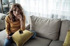 Deprimierte junge Frau, die Schwangerschaftstest hält Stockfotografie