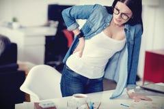 Deprimierte junge Frau, die sich auf dem Tisch lehnt Lizenzfreie Stockfotos