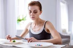 Deprimierte junge Frau, die versucht zu essen Lizenzfreie Stockfotografie
