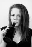 Deprimierte junge Frau, die von einer Weinflasche trinkt Stockbilder
