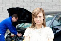 Deprimierte junge Frau, die vor ihrem Auto steht Lizenzfreie Stockfotos