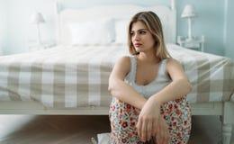 Deprimierte junge Frau, die zu Hause auf Bett sitzt Stockbilder