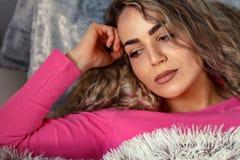 Deprimierte junge Frau, die zu Hause liegt Stockfotos