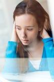 Deprimierte junge Frau, die zu Hause sitzt Stockfoto