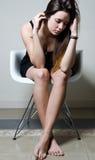 Deprimierte junge Frau, die zu Hause sitzt Stockfotos