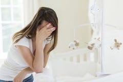 Deprimierte junge Frau im Babyraum Lizenzfreie Stockfotografie