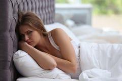 Deprimierte junge Frau im Bett Stockfoto