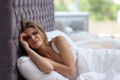 Deprimierte junge Frau im Bett Stockbilder
