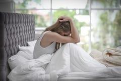 Deprimierte junge Frau im Bett Lizenzfreies Stockbild