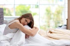 Deprimierte junge Frau im Bett Stockfotografie