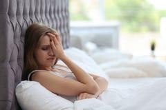 Deprimierte junge Frau im Bett Lizenzfreie Stockbilder