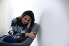 Deprimierte junge Frau im Lehnsessel Lizenzfreie Stockbilder
