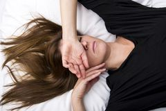 Deprimierte junge Frau liegt in ihrem Bett und bedeckt ihre Augen Stockbilder