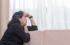 Deprimierte junge Frau sitzen auf Sofa, Lizenzfreies Stockfoto