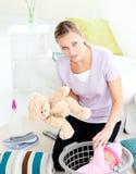 Deprimierte junge Mutter, die Spielzeug in einen Korb setzt Lizenzfreie Stockbilder
