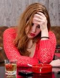 Deprimierte junge trinkende und rauchende Frau Stockfoto