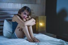 Deprimierte lateinische Frau, die auf Bett durchdachtem und besorgtem abou sitzt Lizenzfreies Stockbild