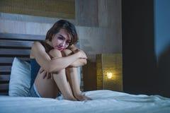 Deprimierte lateinische Frau, die auf Bett durchdachtem und besorgtem abou sitzt Lizenzfreie Stockfotografie