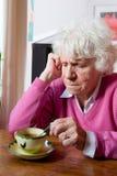 Deprimierte ältere Frau, die am Tisch sitzt Stockfotografie