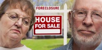 Deprimierte ältere Paare vor Zeichen und Haus der gerichtlichen Verfallserklärung Stockfotos
