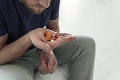 Deprimierte männliche Person, die Tabletten hält Lizenzfreies Stockbild