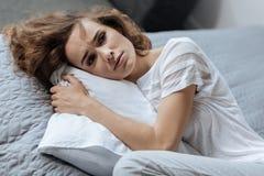 Deprimierte müde Frau, die auf dem Kissen liegt Stockfoto