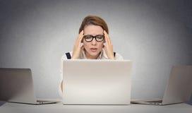Deprimierte müde Frau, die am Schreibtisch vor Laptop stationiert Lizenzfreies Stockfoto