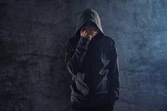 Deprimierte mit Kapuze Person, die auf Wand und dem Schreien sich lehnt Lizenzfreies Stockfoto
