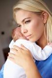 Deprimierte Mutter, die neugeborenes Baby streichelt Lizenzfreies Stockbild