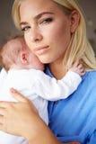 Deprimierte Mutter, die neugeborenes Baby streichelt Stockbild