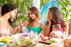 Deprimierte Mutter mit dem Baby, das mit Freunden spricht Lizenzfreie Stockfotos