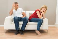 Deprimierte Paare, die auf Sofa sitzen Lizenzfreie Stockfotografie