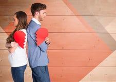 Deprimierte Paare, die defektes Herz halten Lizenzfreie Stockbilder