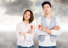 Deprimierte Paare, die defektes Herz halten Lizenzfreie Stockfotos