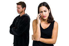Deprimierte Paare, die gegen weißen Hintergrund stehen Stockfoto