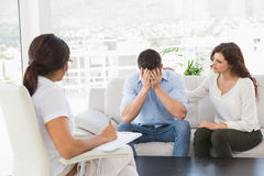 Deprimierte Paare, die mit ihrem Therapeuten sprechen Stockfotos