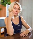 Deprimierte reife Frau, die auf Stuhl sitzt Stockfotos
