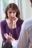 Deprimierte reife Frau, die mit Ratsmitglied spricht Stockbild