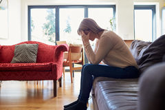 Deprimierte reife Frau, die zu Hause auf Sofa sitzt Lizenzfreie Stockfotos